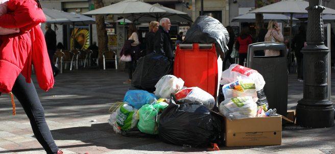 Cubo de basura rodeado de desperdicios