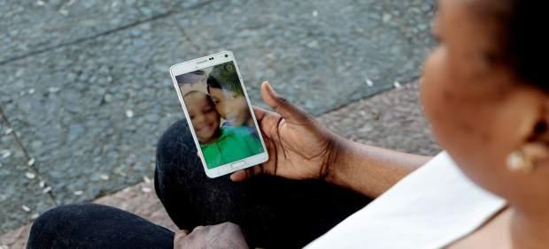 Oumo, mujer costamarfileña que llegó en patera a España, mira la foto de su hijo