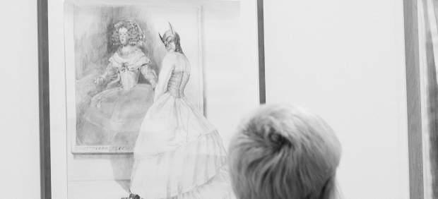Una espectadora frente a una de las obras de Margaret Harrison
