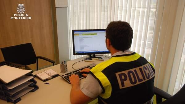 Policia con ordenador, en busca de pedófilos en la red