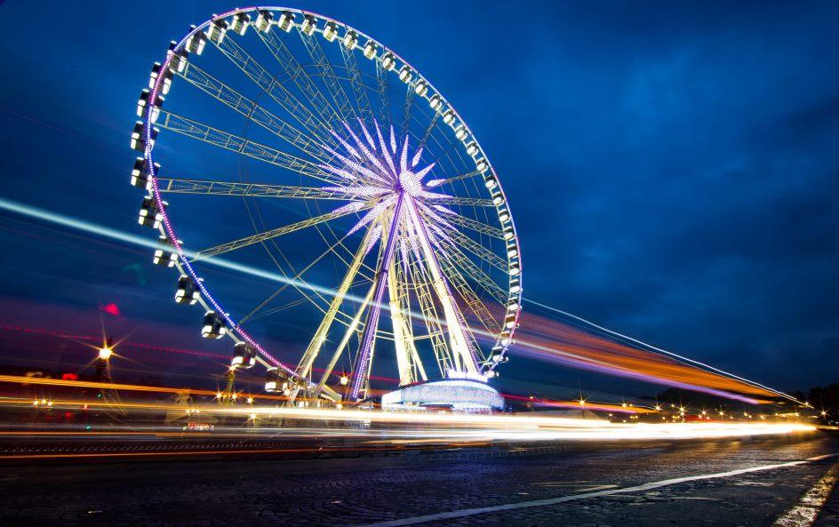 Noria de París. Foto tomada con una velocidad de obturación lenta de vehículos circulan frente a la Noria de París este viernes durante su reapertura, en París (Francia).