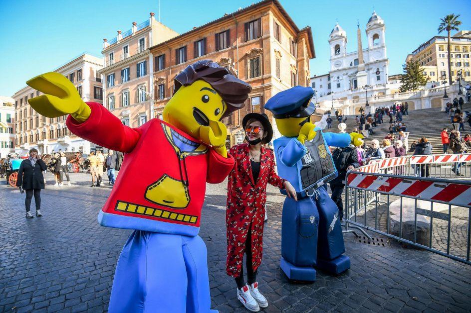 Turista de Lego en Roma. Una turista posa para una fotografía con dos muñecos de Lego que actúan en la Plaza de España, para promocionar la apertura de una nueva tienda de la marca, en el centro de Roma (Italia).