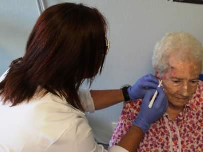 Una enfermera aplicando el tratamiento con luz