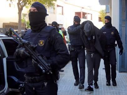 Los Mossos d'Esquadra escoltan a uno de los detenidos durante una operación contra el terrorismo yihadista en Sant Pere de Ribes en la que se han realizado registros a varias viviendas y se han detenido, al menos, a dos personas.