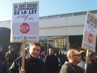 Taxistas con pancartas antes de iniciar la manifestación