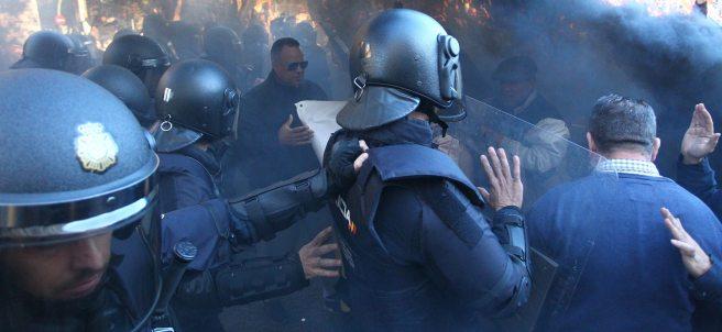 Policías marchan entre el humo de las bengalas