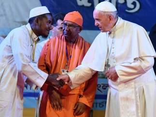 El papa Francisco le da la mano a un refugiado rohingya.