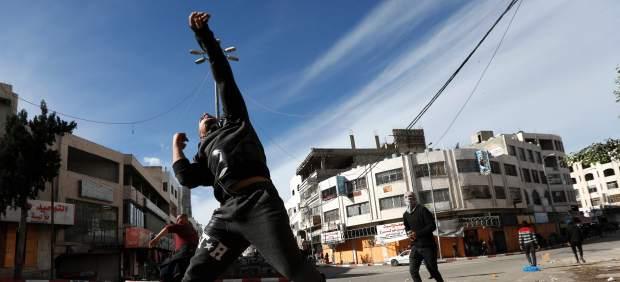 Varios hombres lanzan piedras a las tropas israelíes en Hebrón (Palestina).