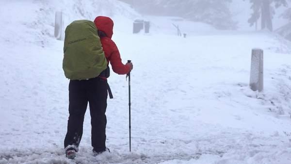 Un hombre pasea por la montaña nevada