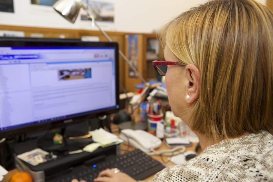 Una mujer trabajando frente al ordenador.