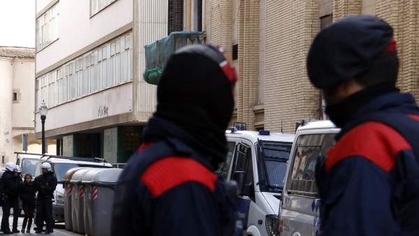 Agentes de la Guàrdia Urbana de Barcelona desalojan a una chica de la Residència d'Estudiants Autogestionada del Raval. En primer plano, dos mossos custodian la entrada a la calle.