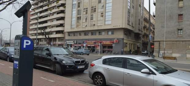 Parquímetro en una calle con coches aparcados en Lleida