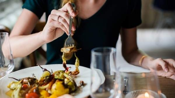 Un cliente degustando un plato en un restaurante.