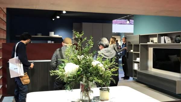 Exposición de un salón con la TV vista a través de una estantería, Feria Mueble