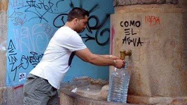 Hombre cogiendo agua.