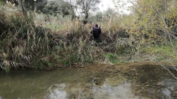 Un policía inspecciona una zona aledaña al río Víboras.