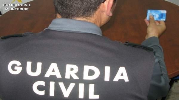Agente de la Guardia Civil con una tarjeta  de crédito