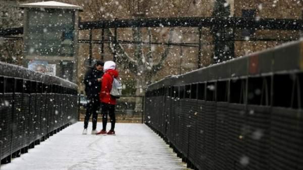 Dos jóvenes debajo de la nieve en el puente de Tordera.