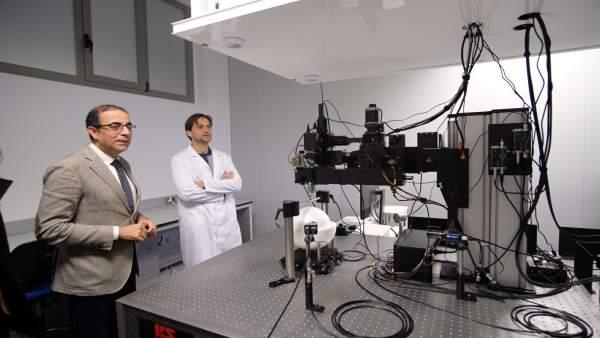 El rector de la US, Miguel Ángel Castro, observa un microscopio multifotón