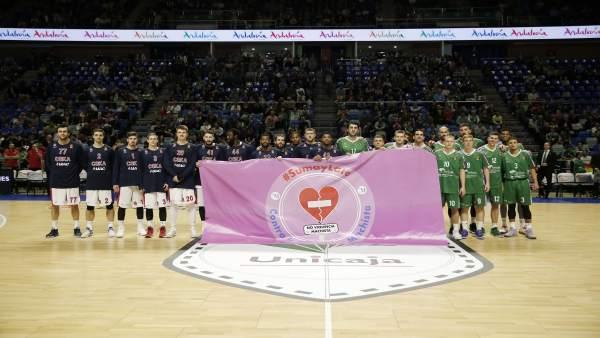 Jugadores del Unicaja con la bandera de No a la violencia machista