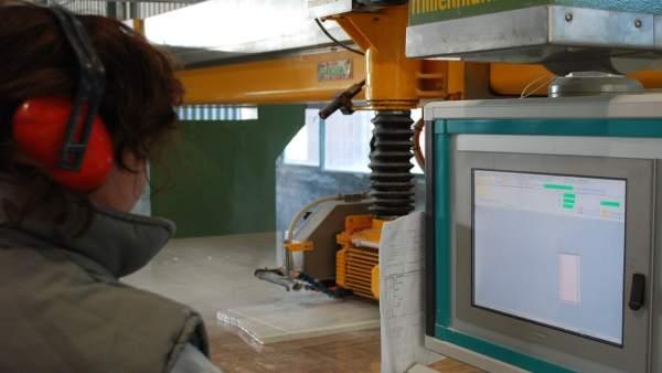 Un operario maneja una máquina de control numérico