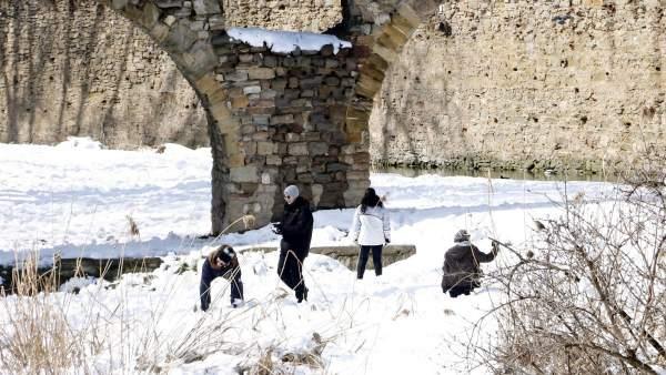 Niños y jóvenes jugando en la nieve en Vic.