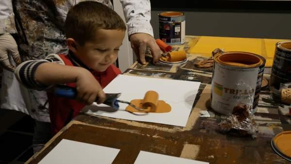 Un niño pinta una tesela que compondrá la réplica de la Inmaculada