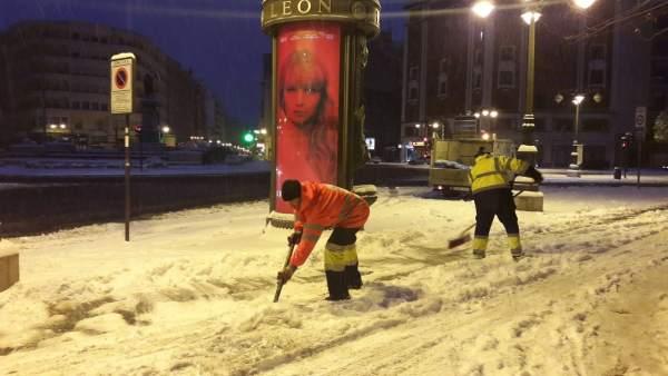 Operarios trabajando por la noche en León ante la nevada