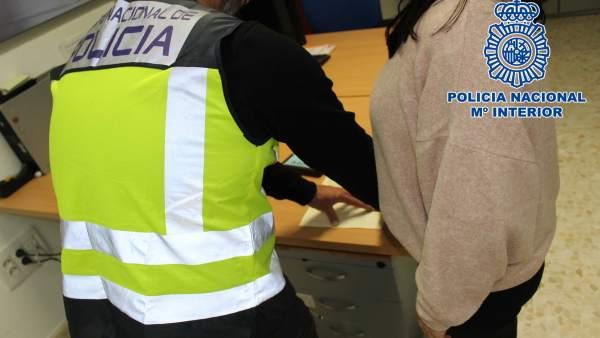 Un agente toma las huellas a una detenida