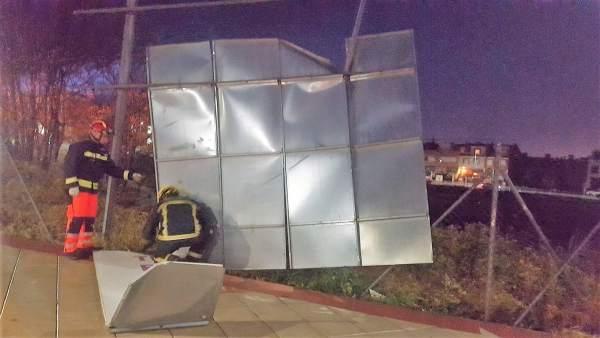 Bomberos intervienen para retirar una valla derribada por el fuerte viento