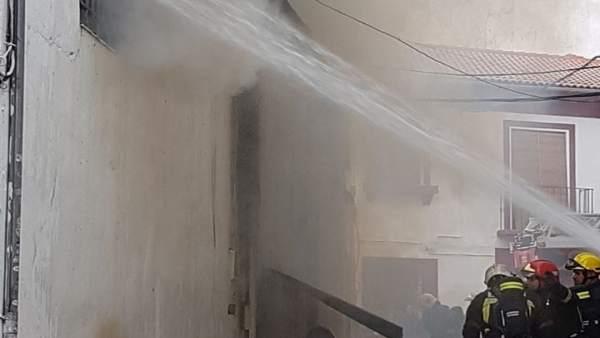 Tareas de refresco en un incendio en un almacén de muebles en Peligros (Granada)