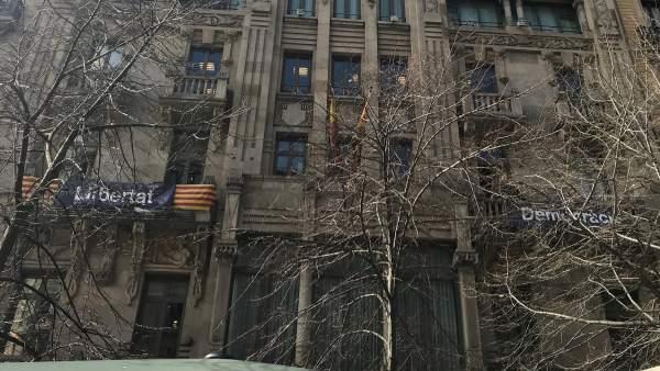 La fachada del departament d'Economia de la Generalitat con las pancartas de 'Democràcia' y 'Llibertat'.