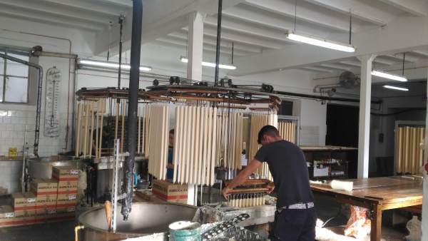 Dos empleados trabajan en la fabricación de velas en la empresa Cera Bellido.