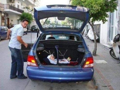 Un padre metiendo en el maletero a su bebé.