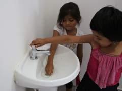 Dos niñas juegan en los baños del colegio de la comunidad Huaytu de Buena Vista