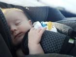 Un bebé duerme en la silla infantil de un coche.