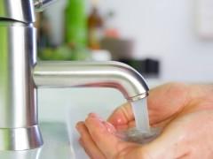 Unas manos sostienen el agua que sale del grifo
