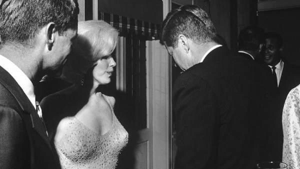 Marilyn Monroe, entre Robert y John Fitzgerald Kennedy, tras cantarle a este último el famoso 'Happy Birthday, Mr. President!', el 19 de mayo de 1962. A la derecha, Arthur Meier Schlesinger; detrás, Harry Belafonte.
