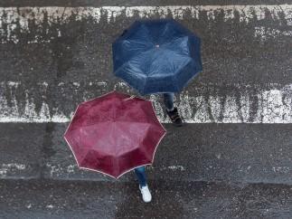 Dos personas portando paraguas