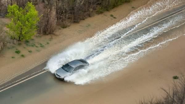 Un coche circula por la recta de Arguedas anegada de agua