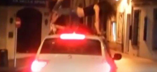 Dos jóvenes bailan sobre el techo de un coche