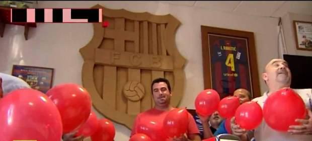 Hinchas sevillanos del Barça con globos rojos