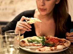 Una mujer, comienzo una porción de pizza