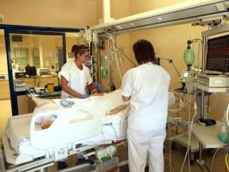 Enfermeras con un paciente en una habitación de hospital.