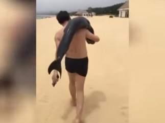 Turista con un delfín al hombro