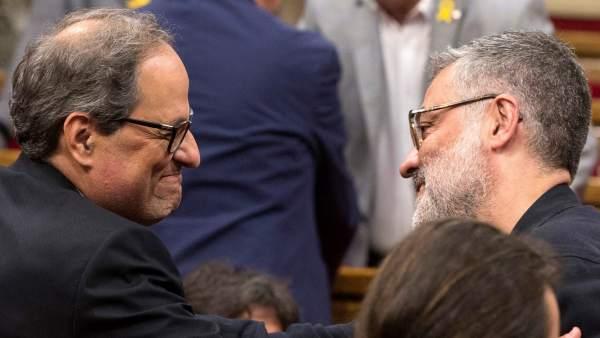 Torra y el portavoz de la CUP, Carles Riera, se saludan en el Parlament.
