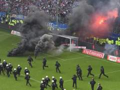 Hinchas del Hamburgo lanzan bengalas en un fondo del Imtech Arena.