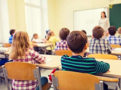 Alumnos atienen a una profesora en un centro educativo