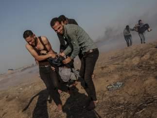 Manifestante palestinos cargan a una mujer herida en la frontera con Israel