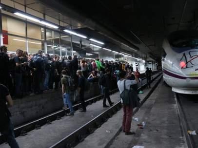 Varias personas acupan la andén de la estación de Sants de Barcelona.